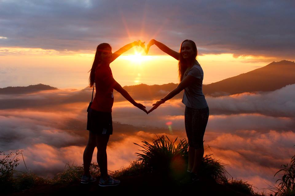 two girl making a heart shape with their arms on top of batur mountain in bali, indonesia