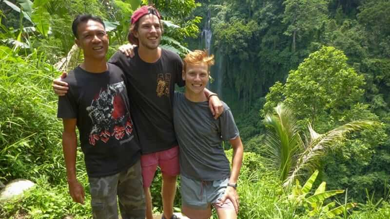 Two guys posing for a picture in the rainforest with a local