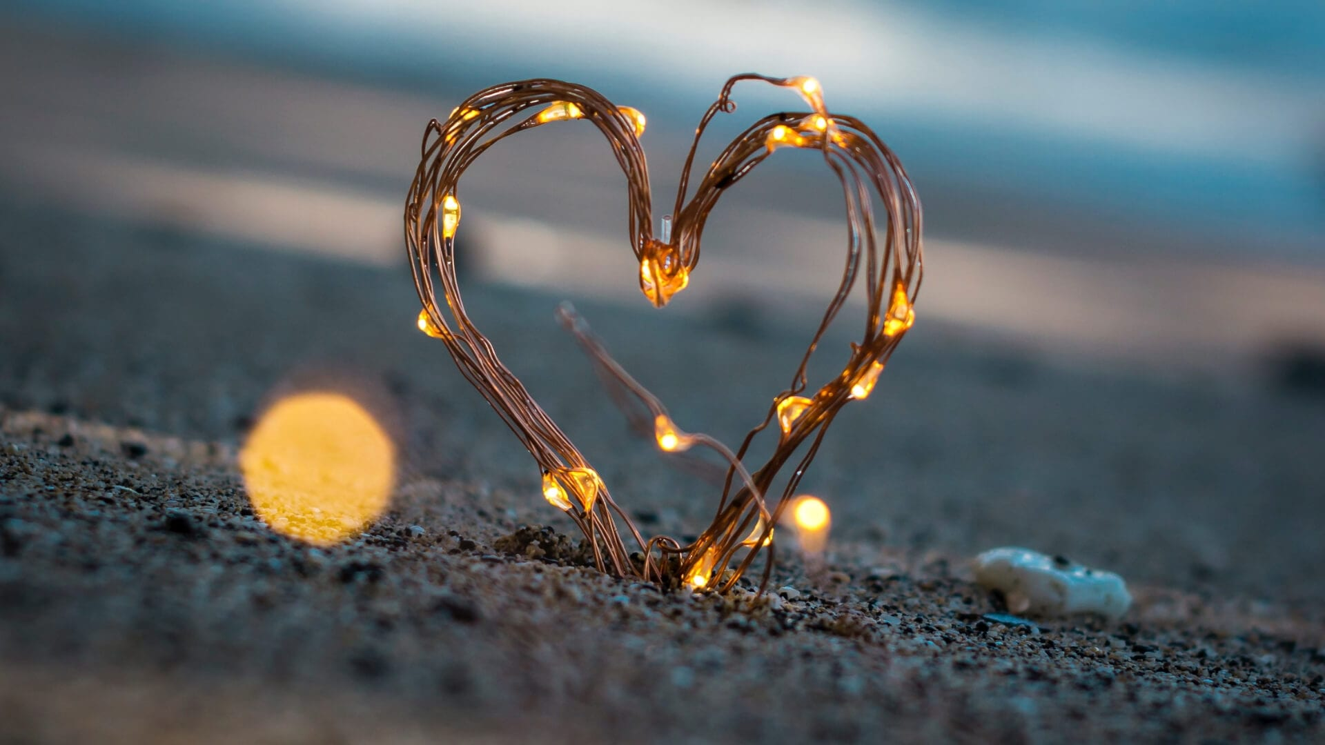 An illuminated heart is standing on a beach during sunset.