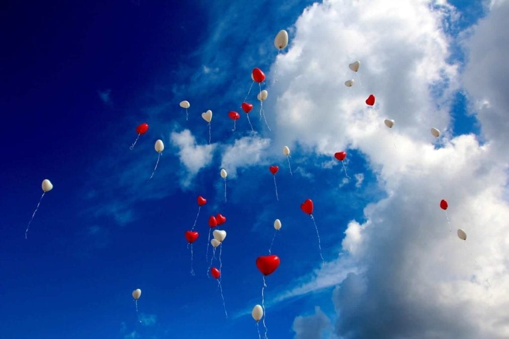 white and red balloons are floating under a clear blue sky