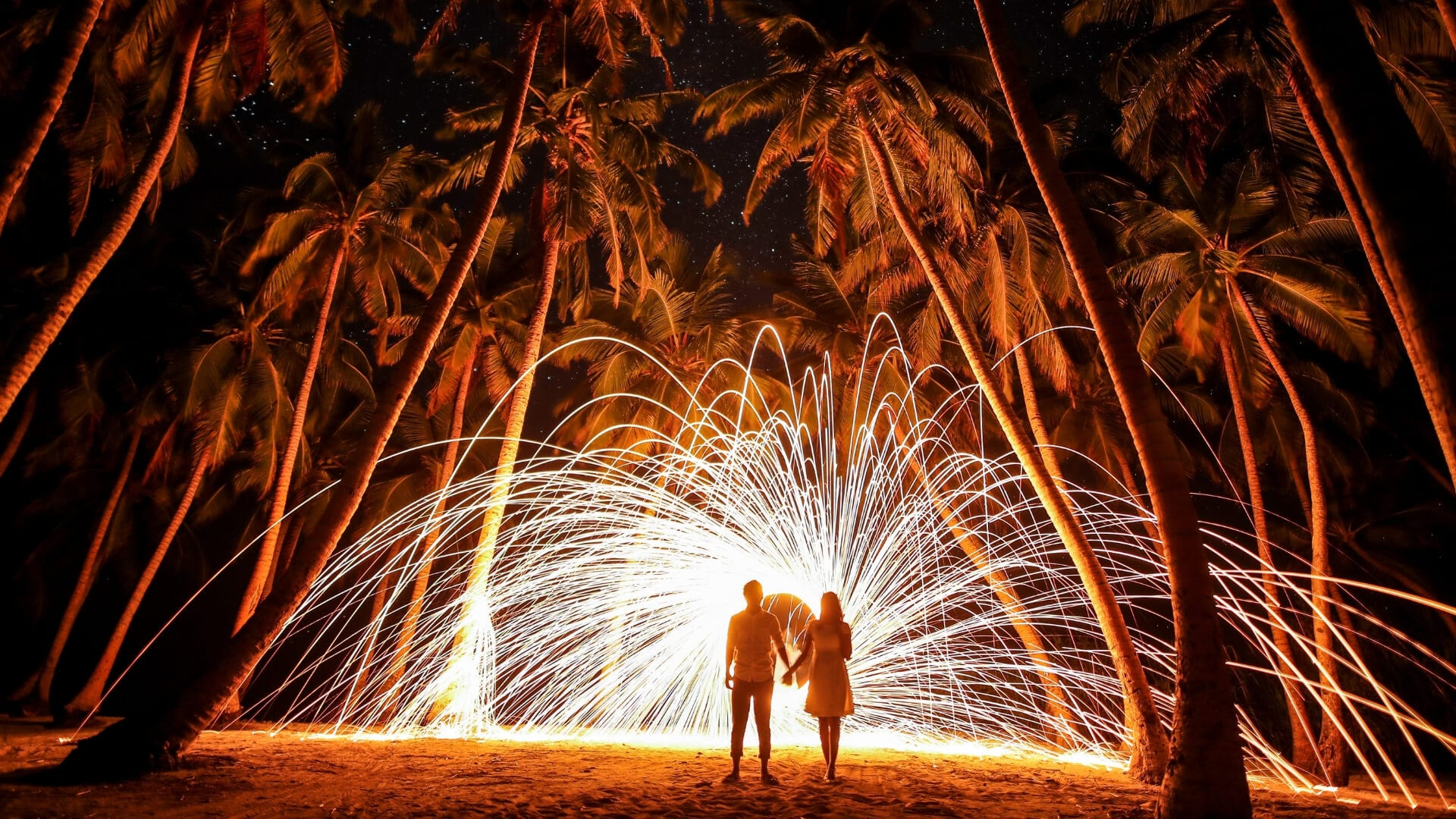 A couple is walking under palm trees and fireworks on their honeymoon on a beach.