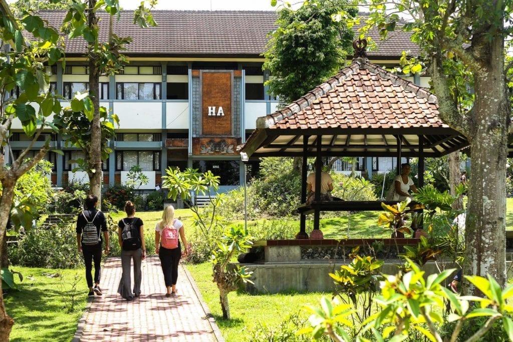 3 students walking on the campus of Udayana University