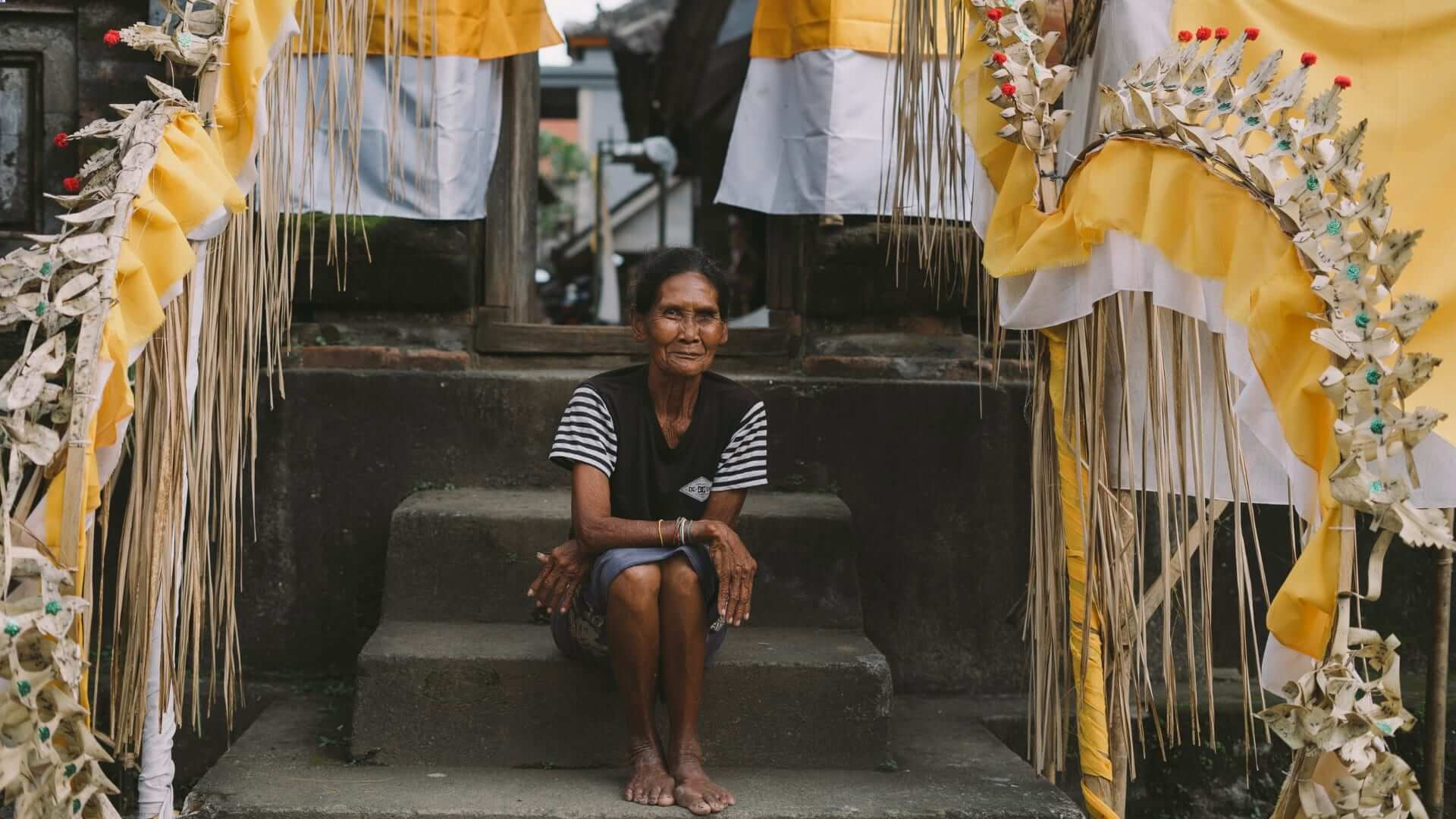 An Indonesian woman is sitting in front of a temple in Bali.