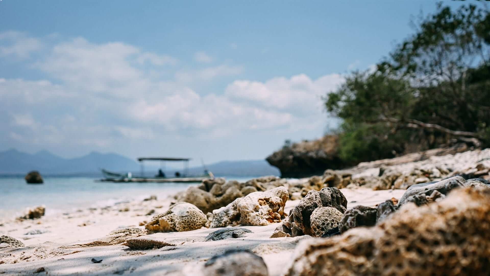 A white beach with small rocks and a boat in Indonesia.