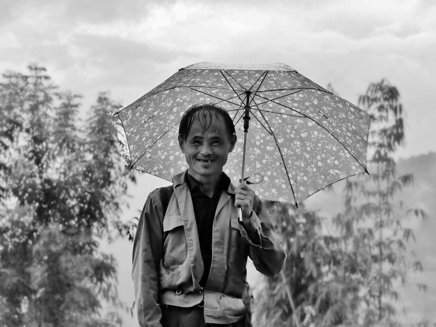 old man smiling to the camera with umbrella