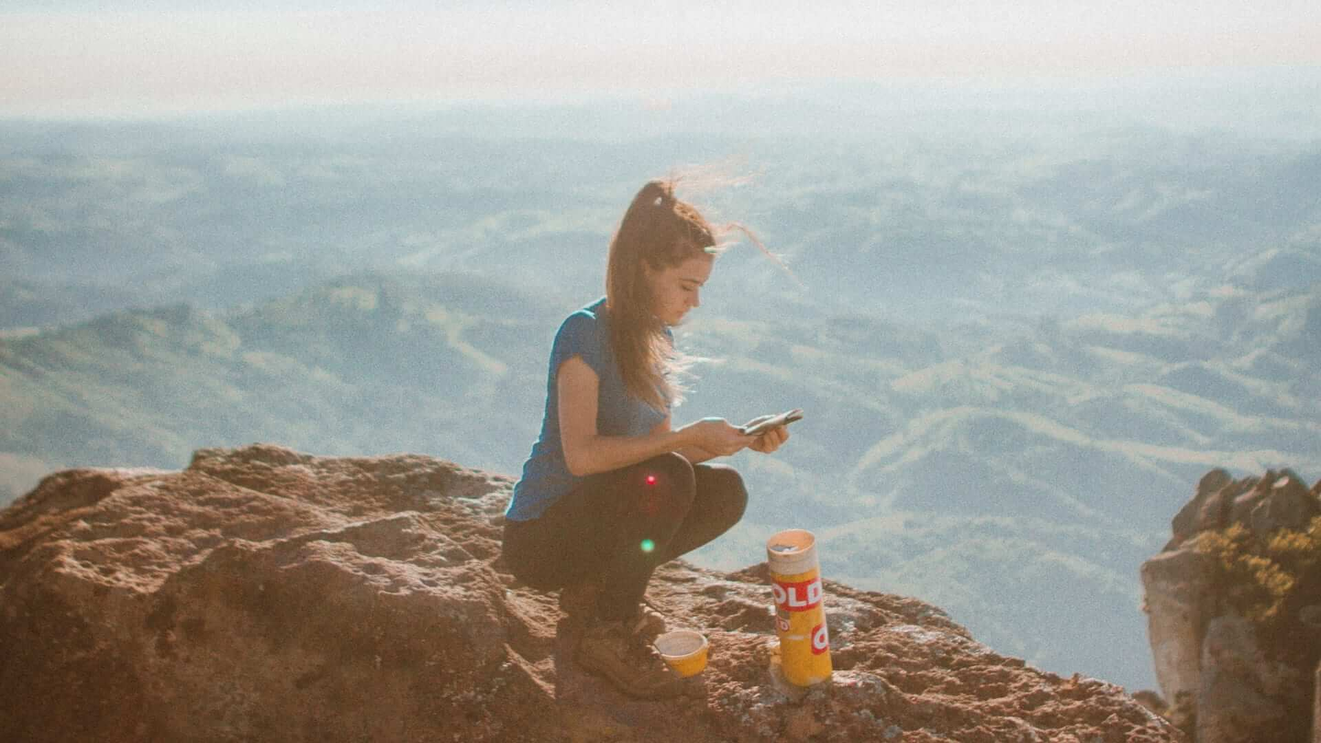 A woman is sitting in a squatting position and holding a phone on a mountain in Brazil.