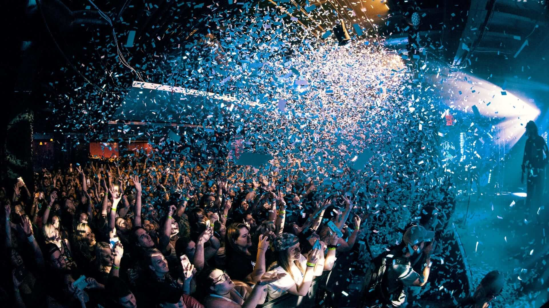 People are dancing with their hands up and confetti is falling from the top of a club in America.
