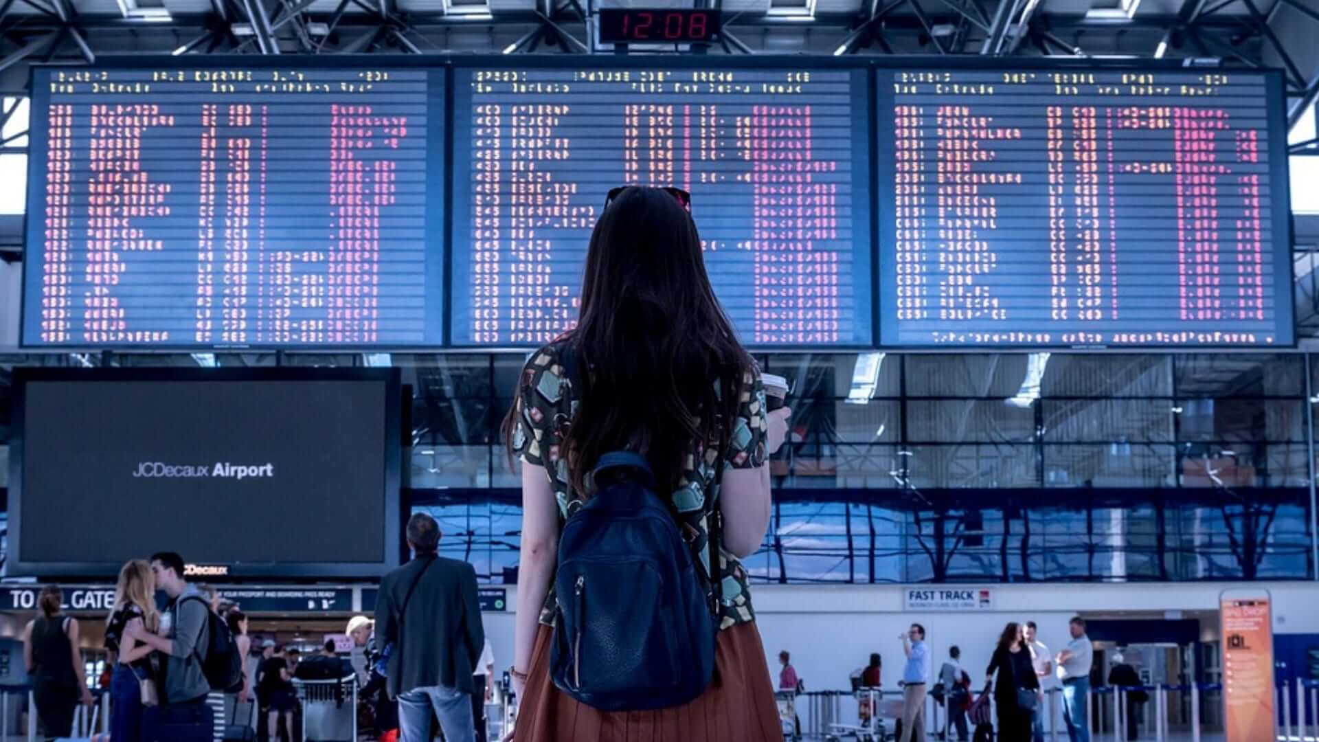 A girl is standing in front of flight information signs on an airport.