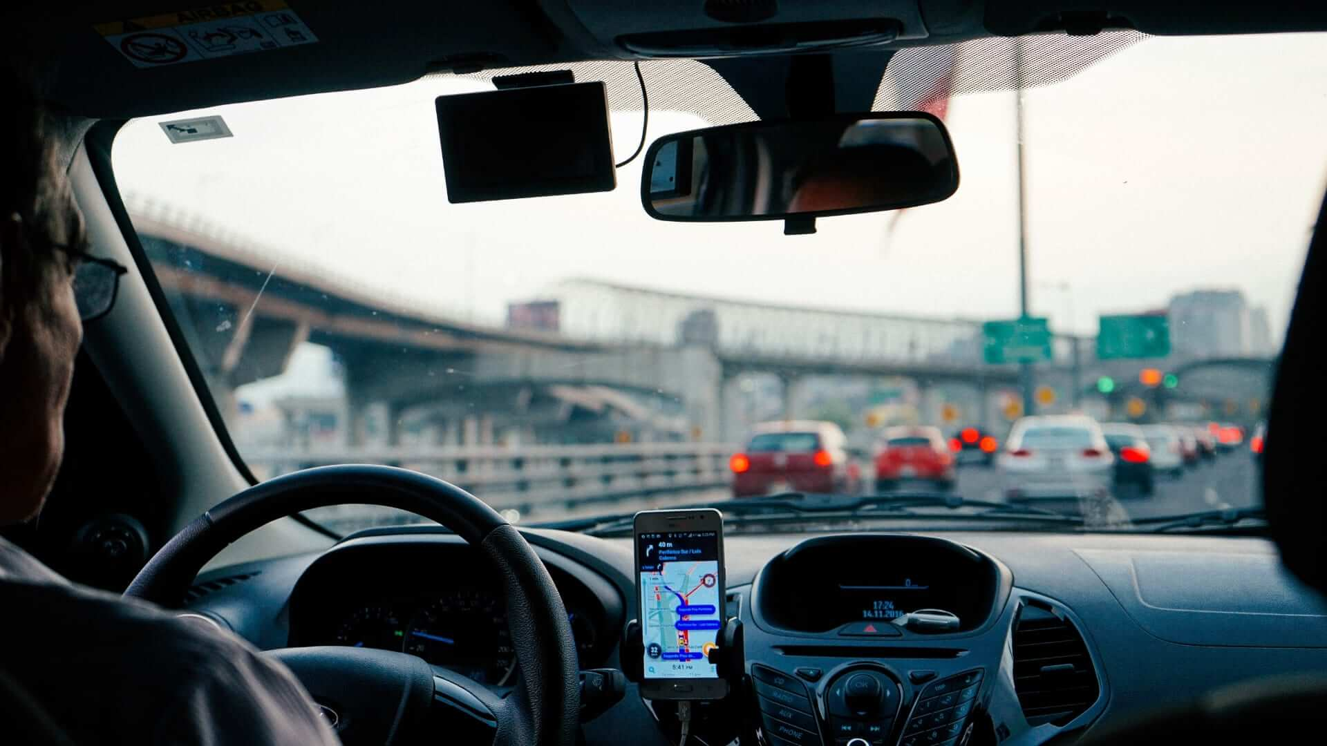 A man is driving a car with a phone with navigation on it in the car.