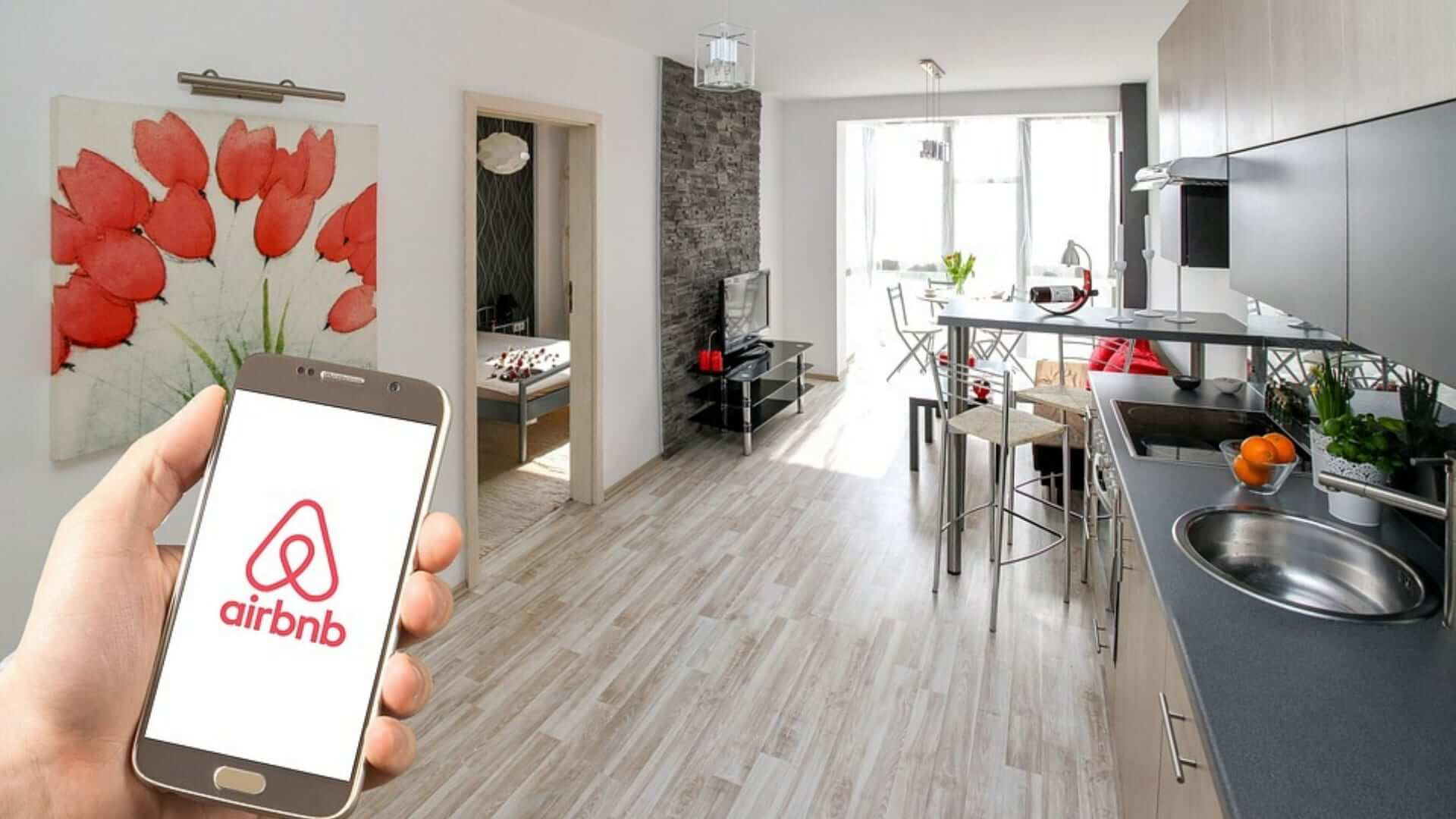 A person is holding a Samsung phone with the Airbnb application in front of an appartment.