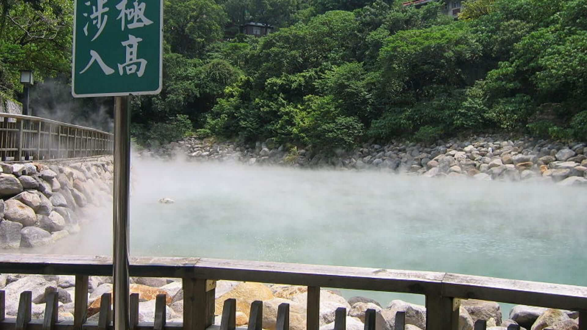 A bridge and a green plate in front of steaming water in Taiwan.