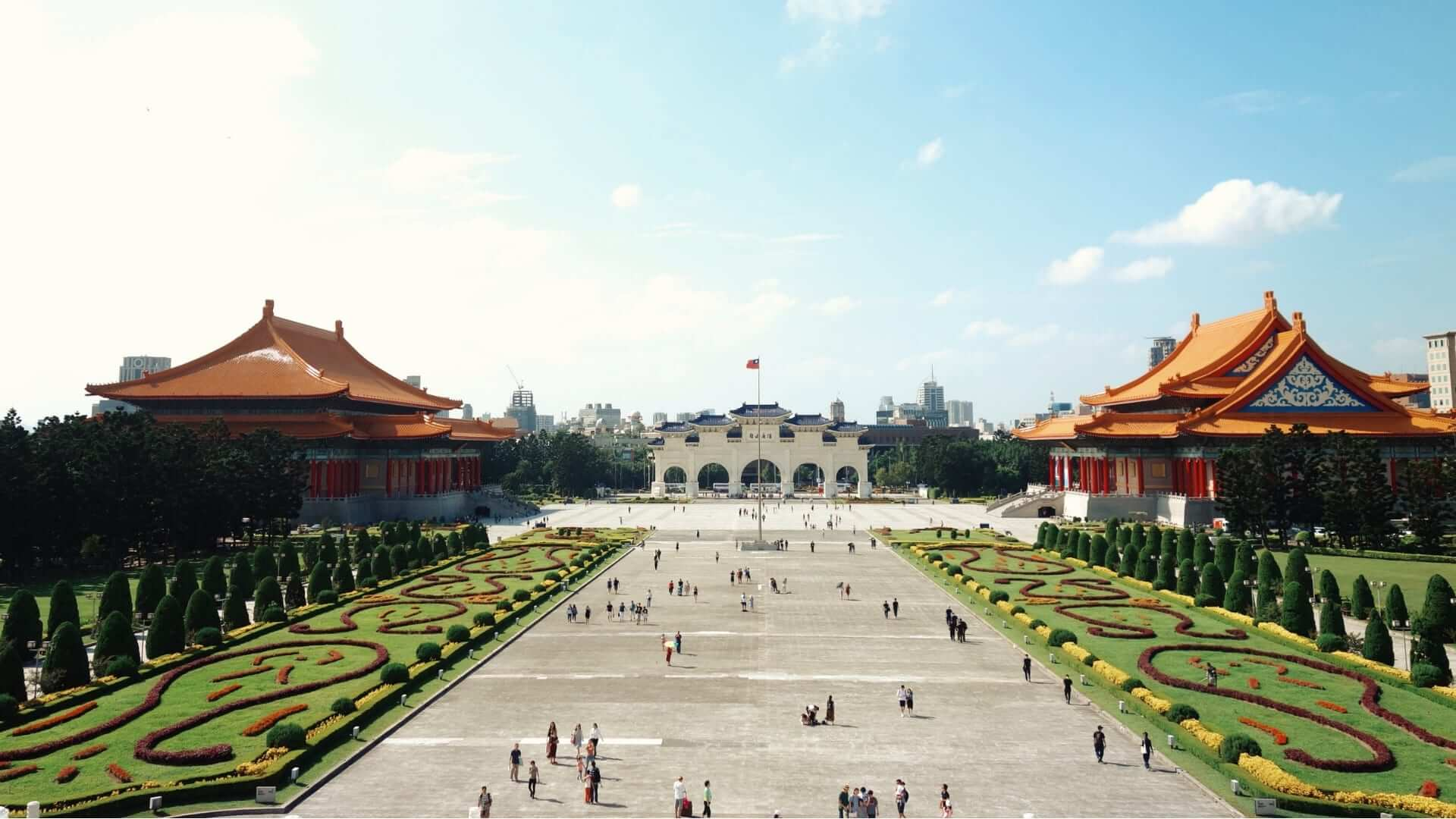 People are walking on a big square in a garden that is leading to a white temple in Taiwan.
