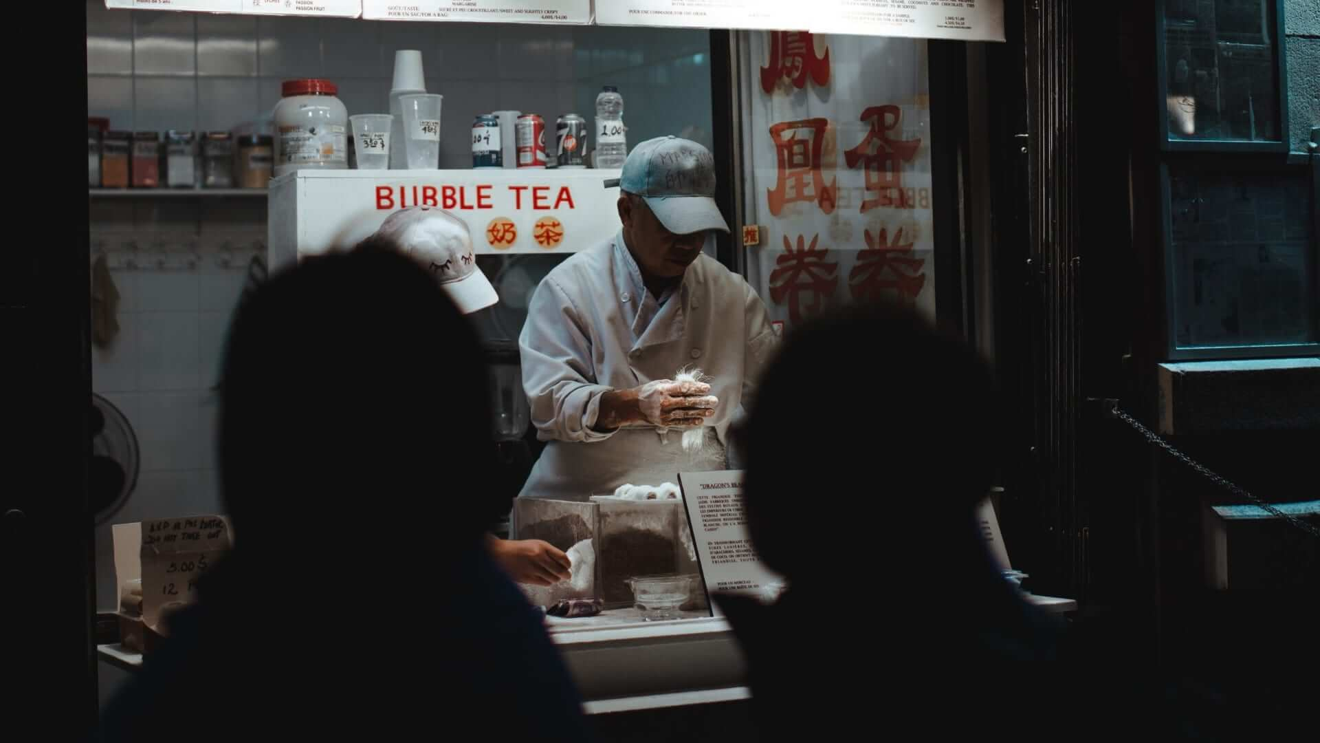 A man is selling bubble tea from a stall in the evening where there are two people waiting in Taiwan.