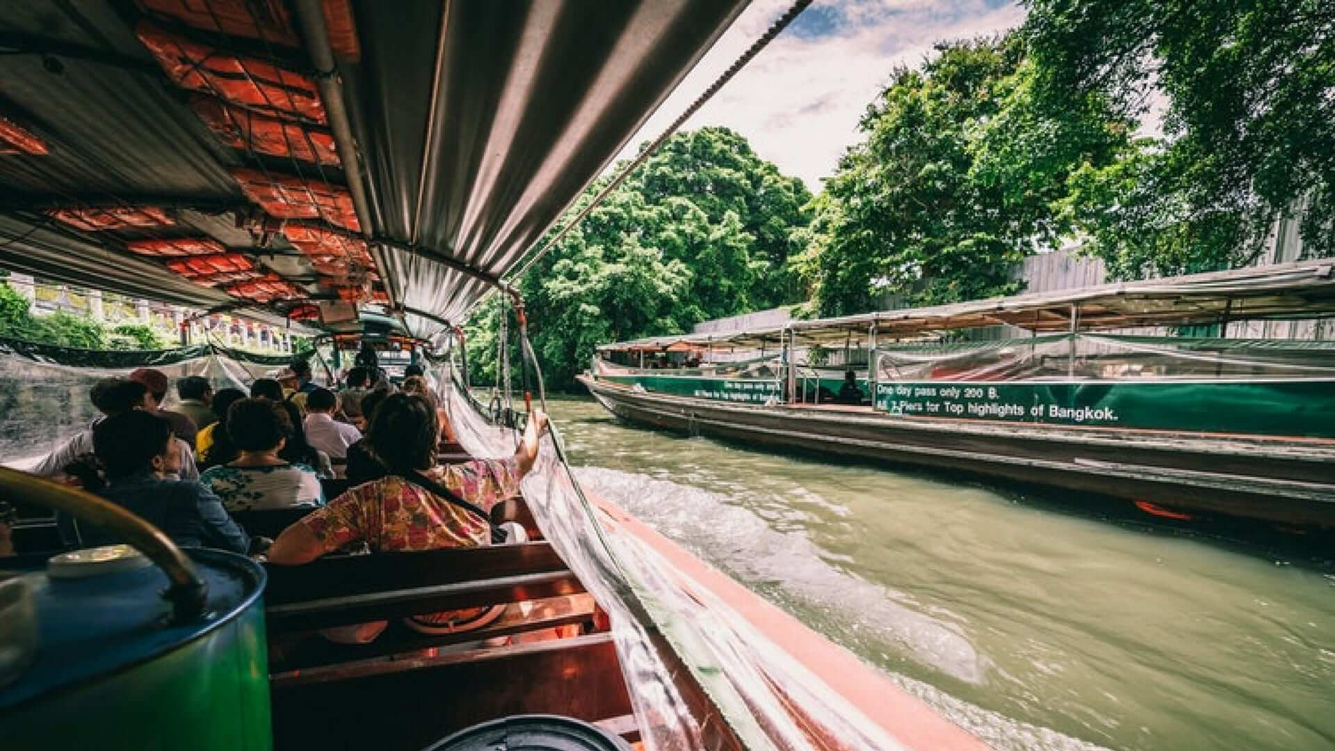 A picture made from a sailing boat of another boat in a river in Bangkok.
