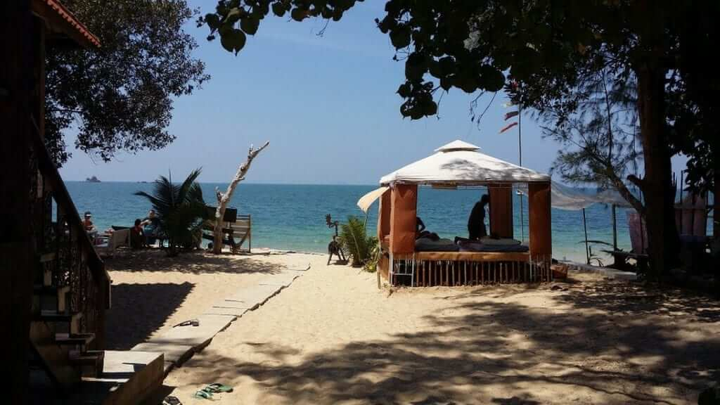 A person is getting a Thai Massage in a small open beach cottage at a beach near Bangkok.