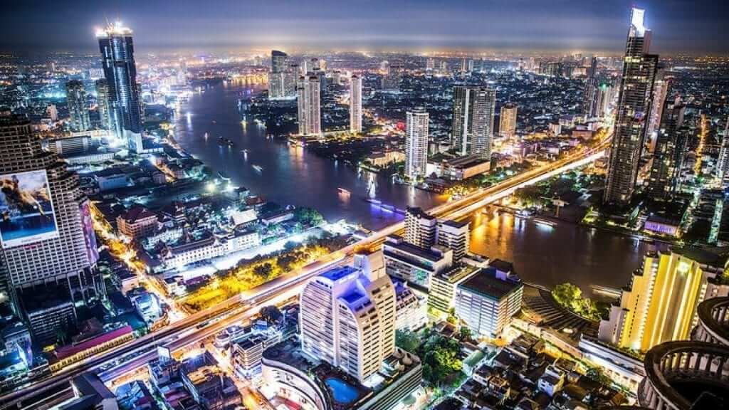 A view of illuminated buildings and a river during nighttime in Bangkok.