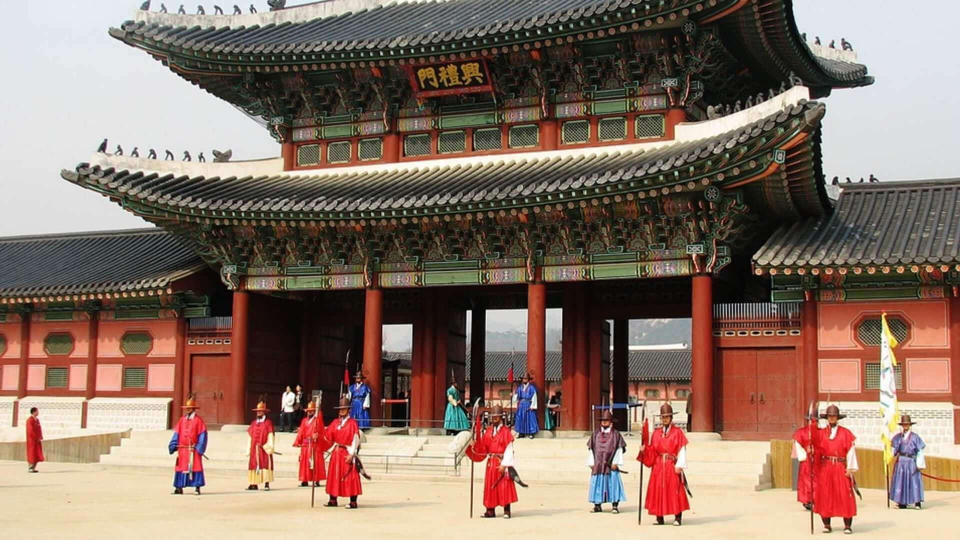 Korean armed guards in traditional outfits are standing in front of a palace in Seoul.