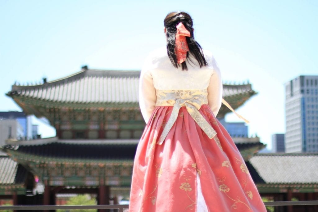 A woman wearing a traditional Asian costume in front of the Gyeongbokgung Palace