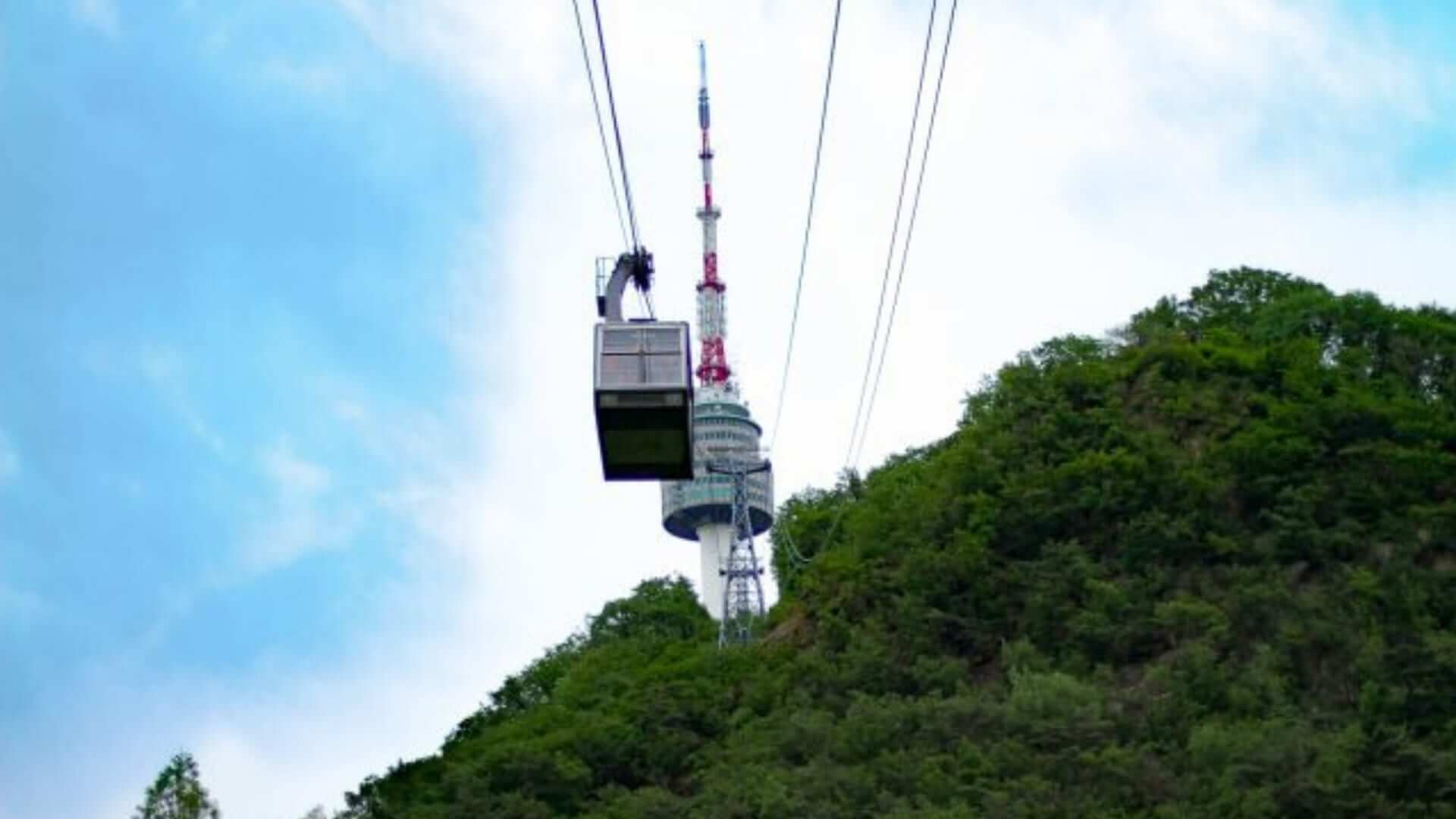People are going by cable car up a hill to visit the Seoul Tower in South-Korea.