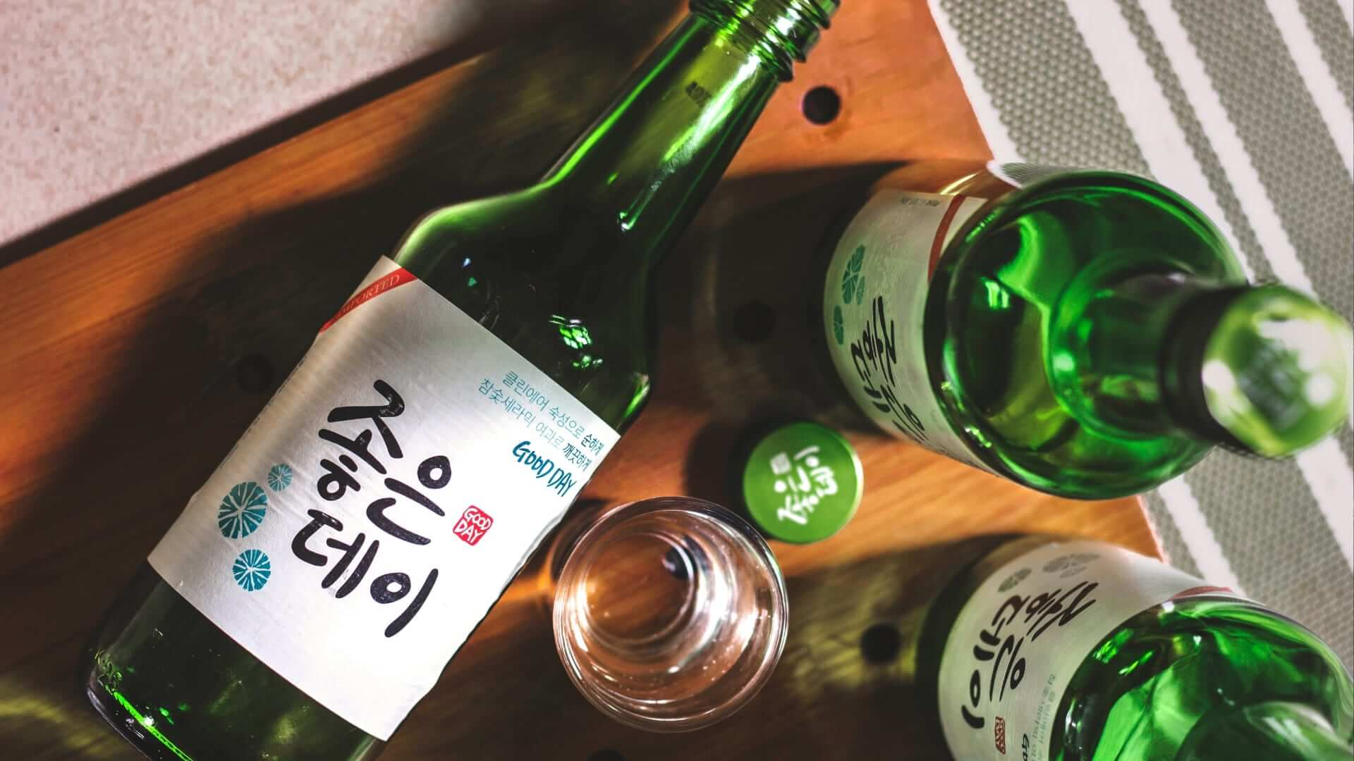 A shot glass is standing in the middle of three green bottles with Korean text on it in Seoul.