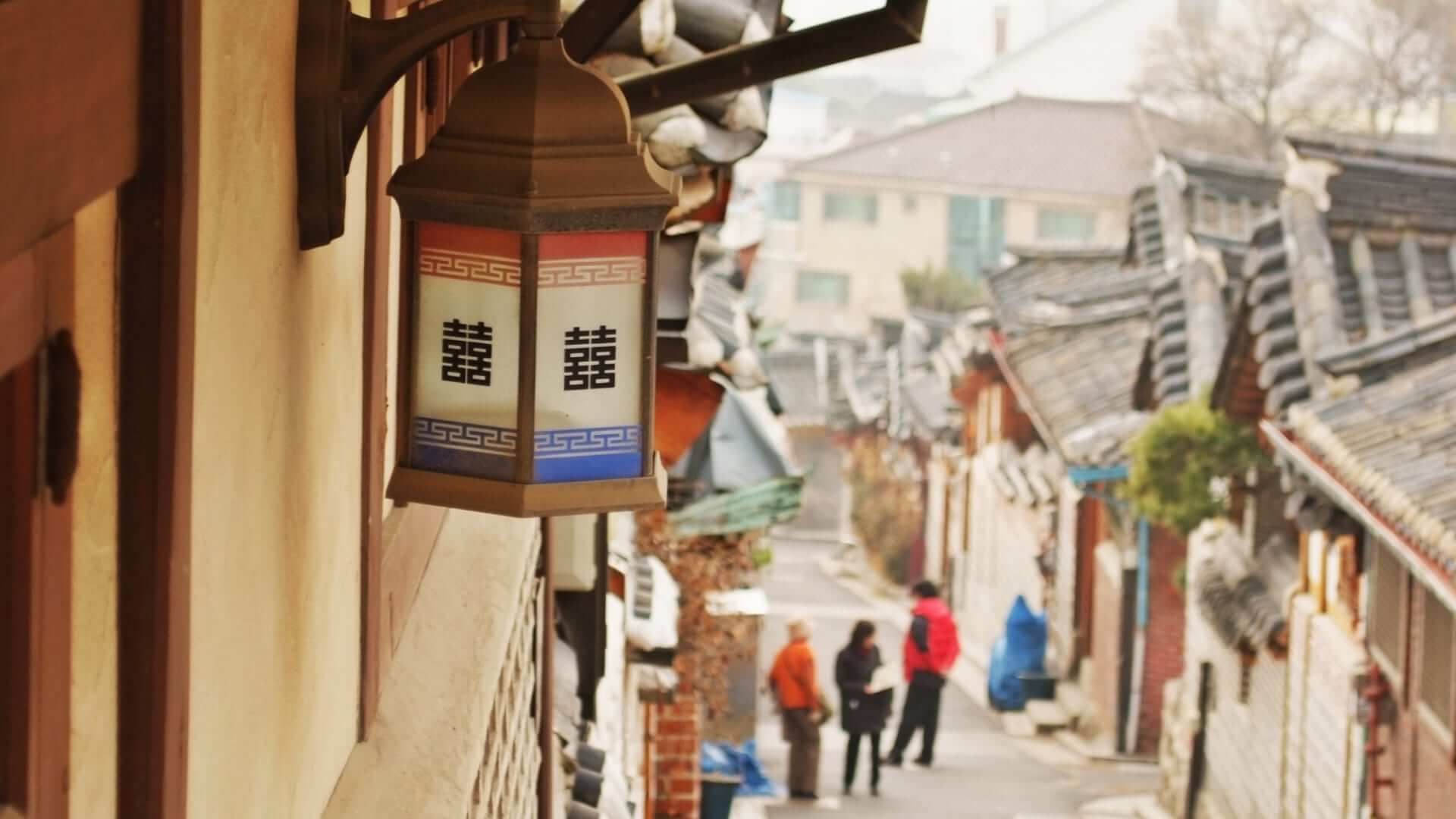 People are walking on a street in a traditional Korean village in Seoul.