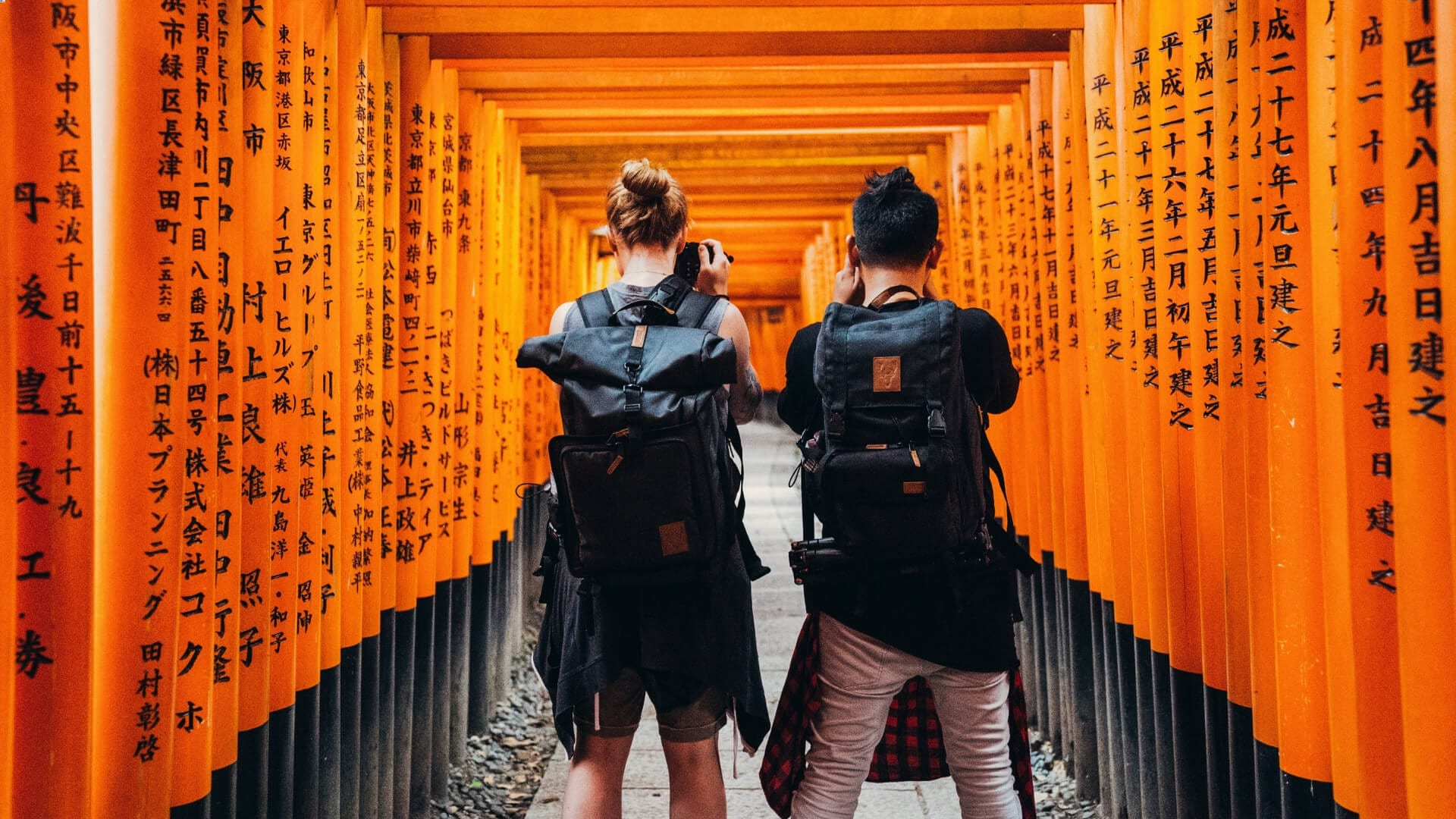 Two men are standing in a tunnel made of orange poles while they are making a picture in China.