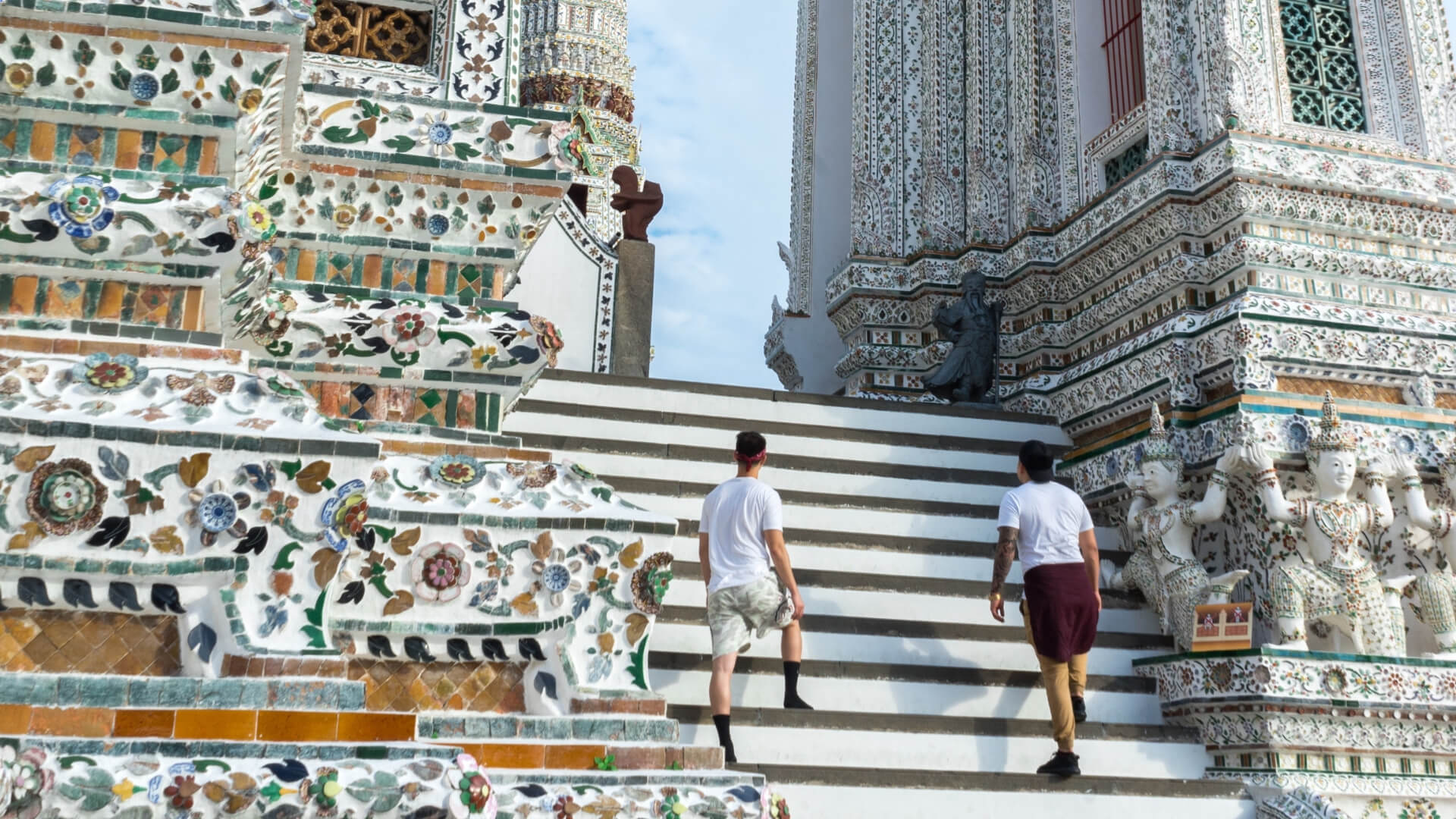 Two men are walking on the stairs of a white temple in Thailand.