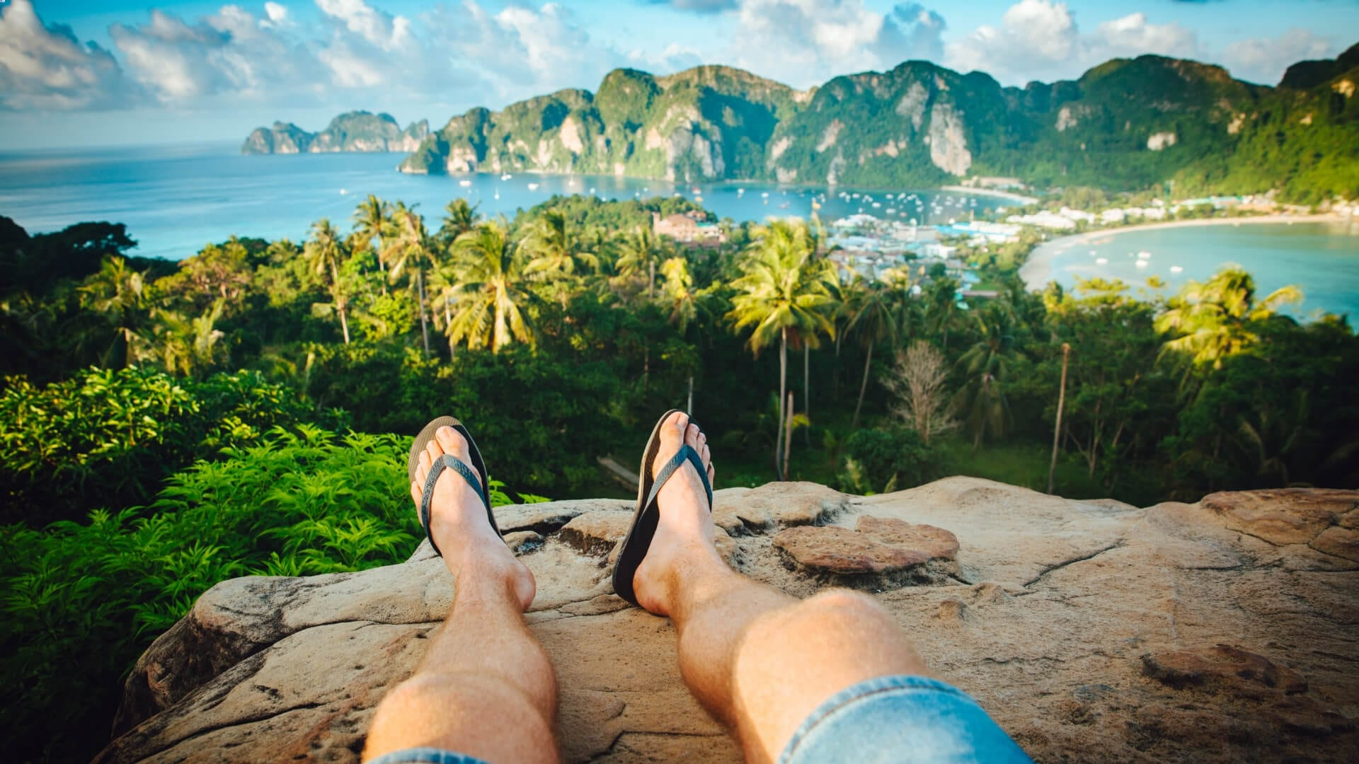 A person is laying on a rock in front of palm trees and a sea in Thailand.