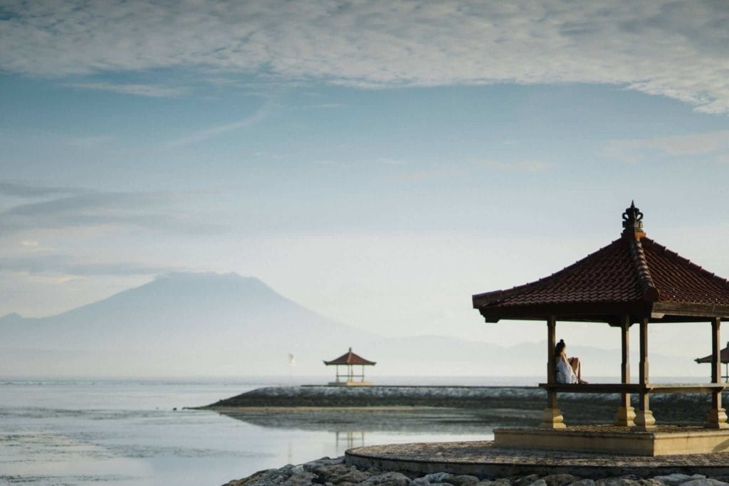 Girl enjoying the peacefulness under a traditional hut by the ocean in Bali