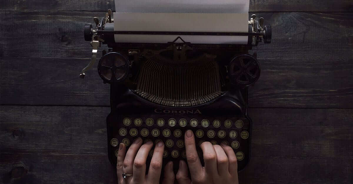 A person is writing on an old school typewriter.