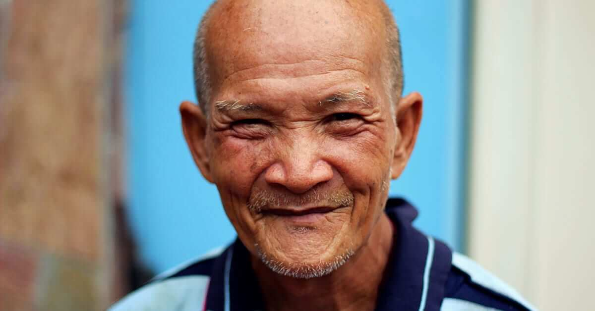 An older local guy from Bangkok is smiling into the camera.