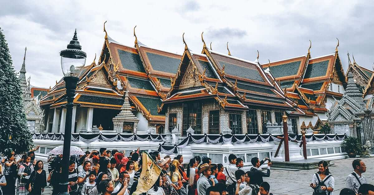 Group of people taking photos of a big temple in Bangkok.