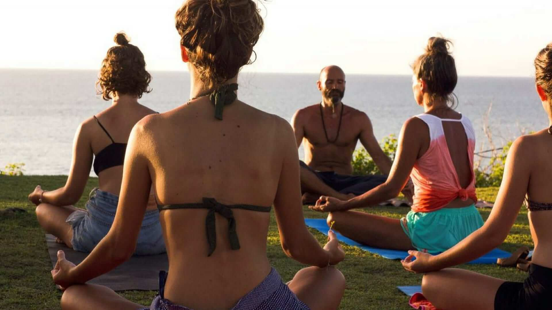 A group of girls are doing yoga with a male yoga teacher on a cliff at Balangan Beach.
