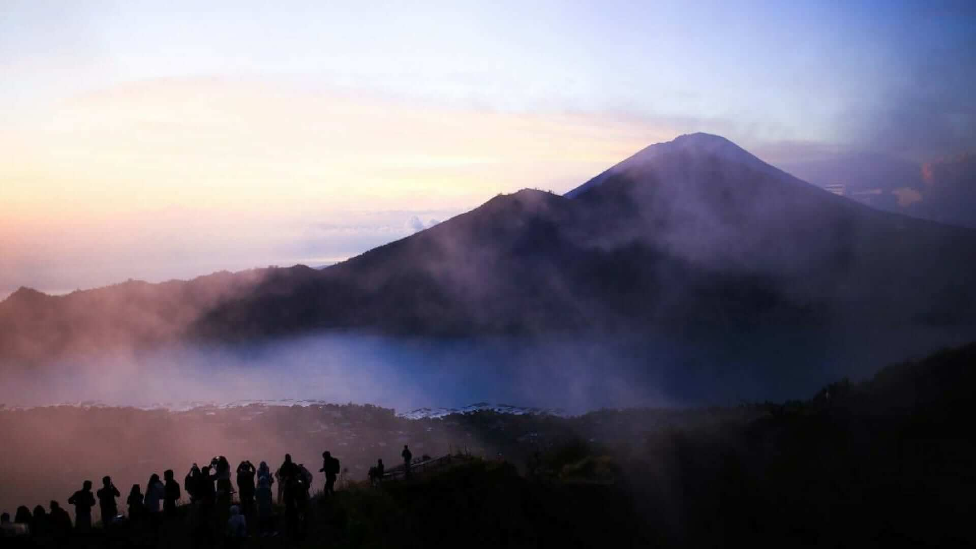 Silhouette of people hiking on Mount Batur early in the morning in Bali.