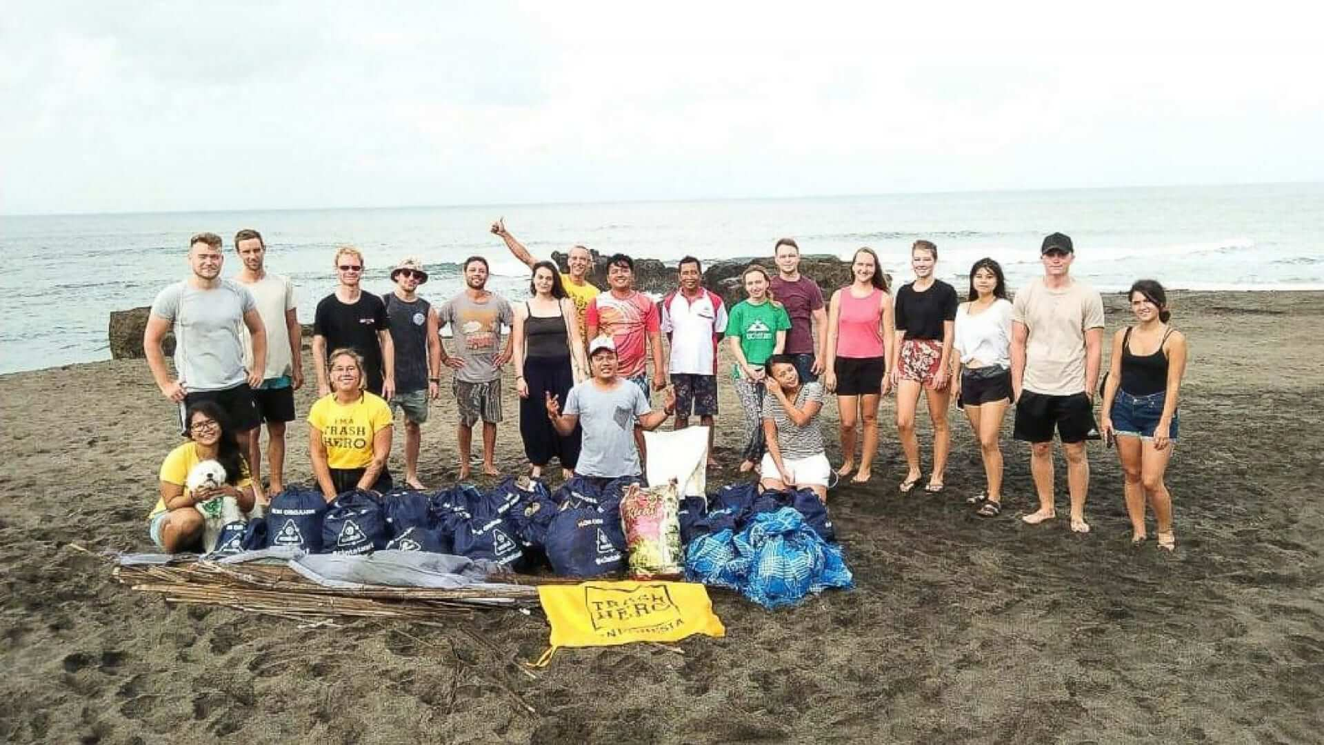 A group picture of students and filled garbage bags at the beach in Bali.