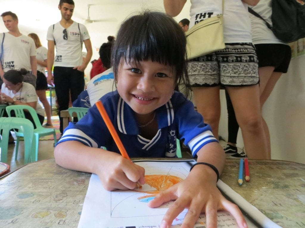 Girl smiling at the camera while drawing and colouring