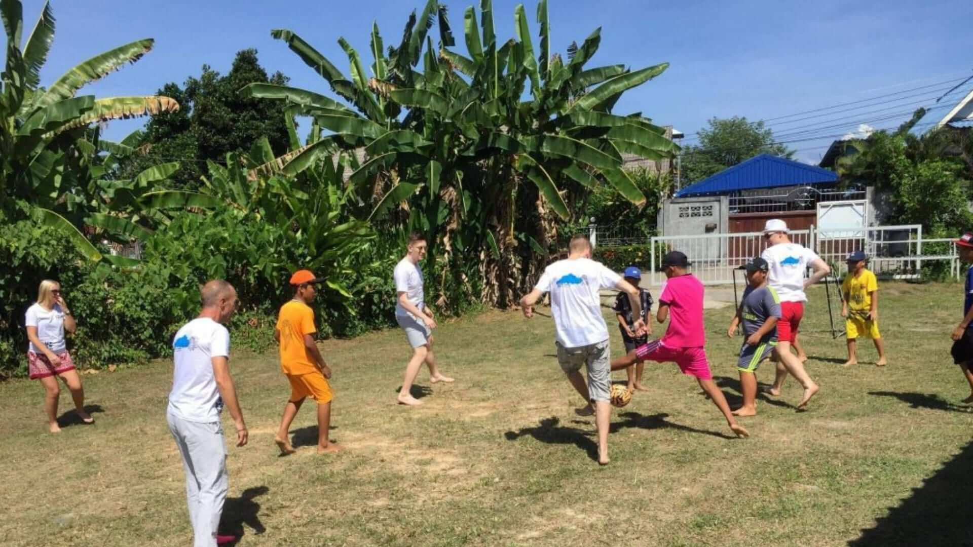 Students are playing soccer with Thai children in Phuket.