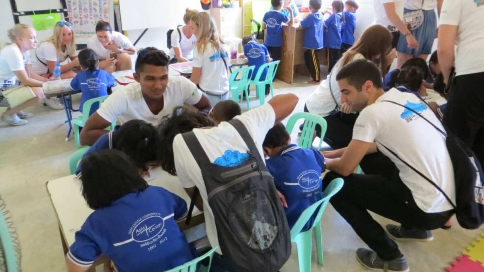 Exchange students are talking and working together with children in Thailand.
