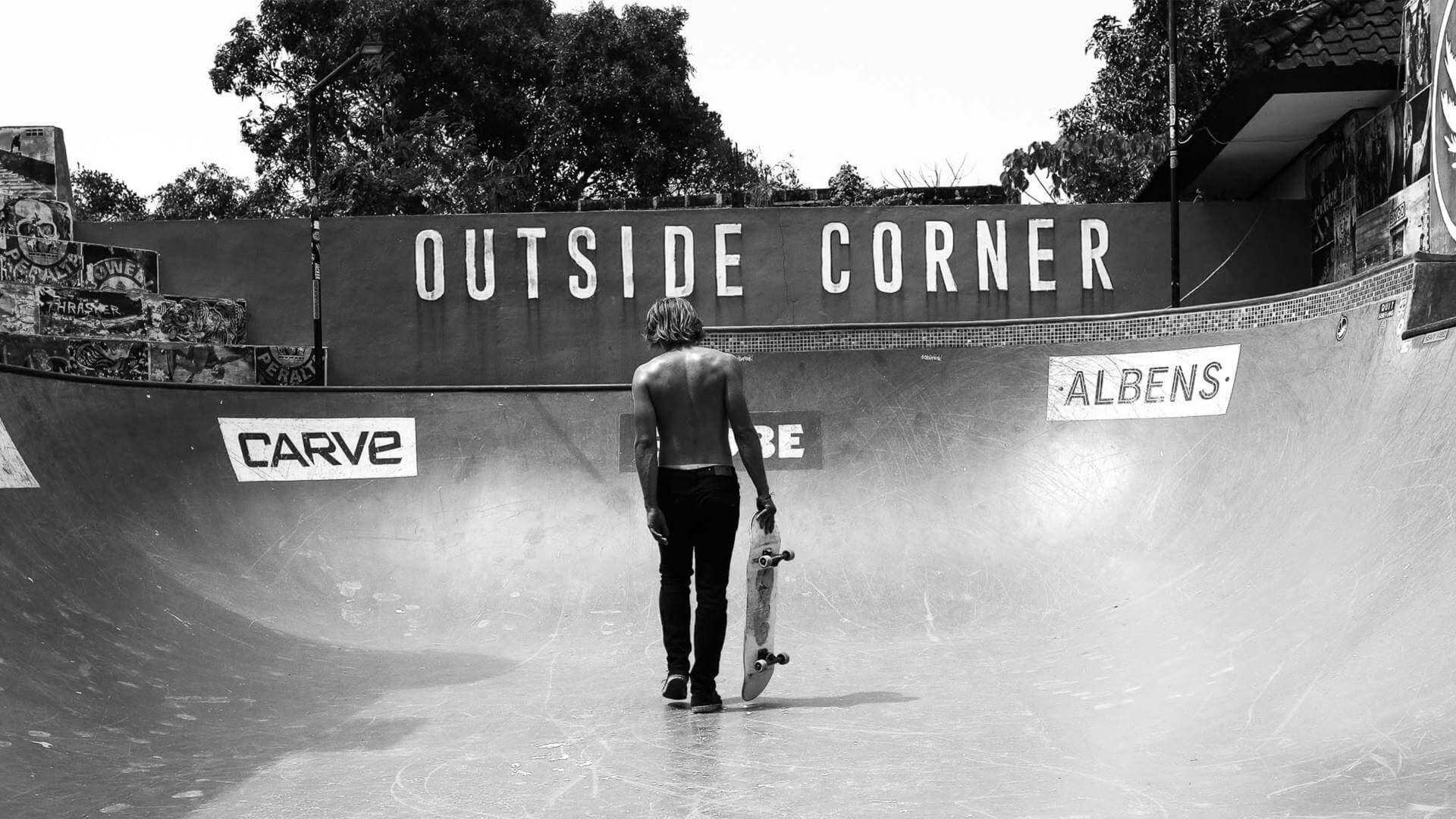 Black and white photo of a guy standing in the middle of a pool in Uluwatu with his skateboard in his hand.