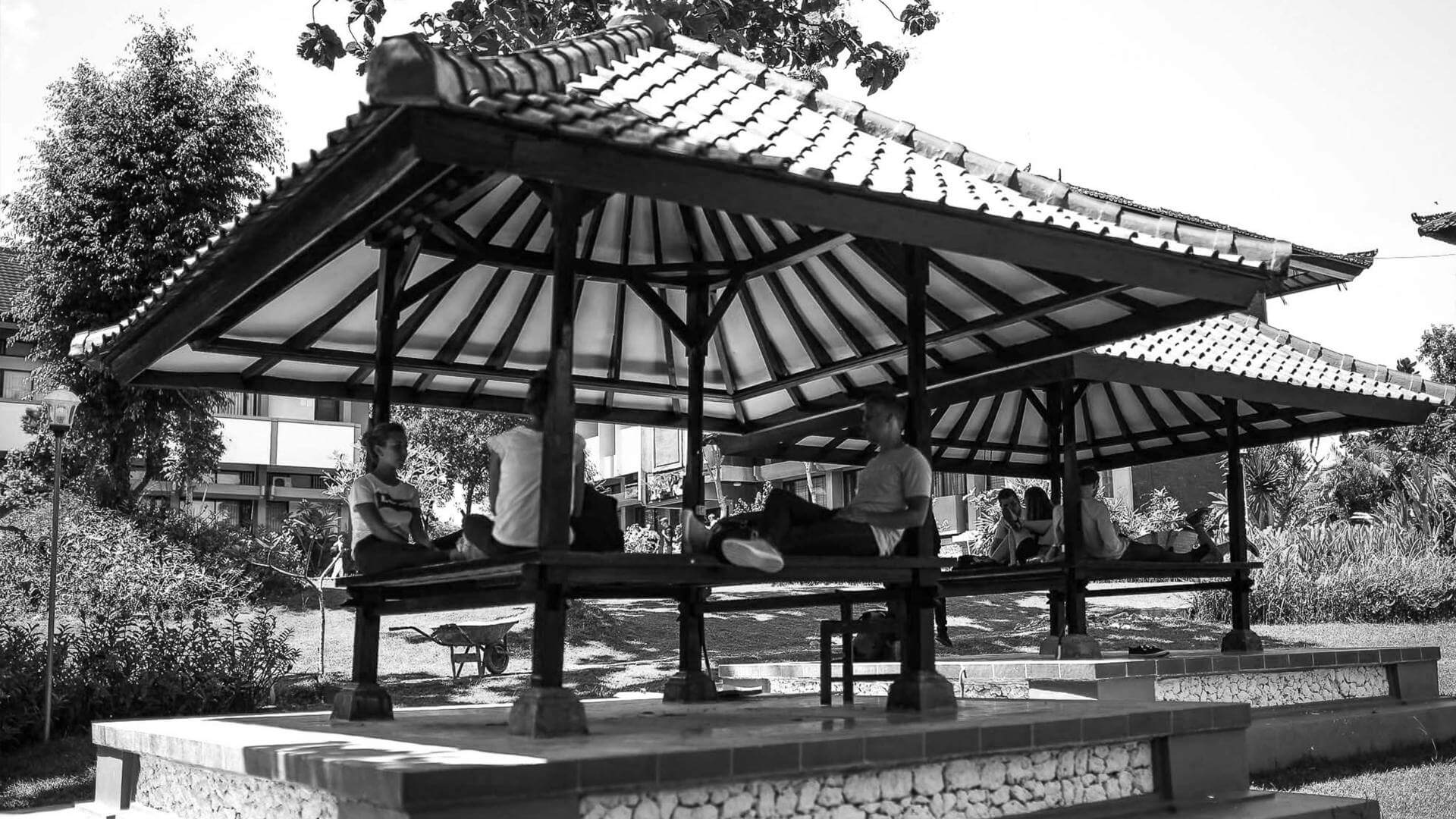 Black and white photo of people sitting in the shade and talking.