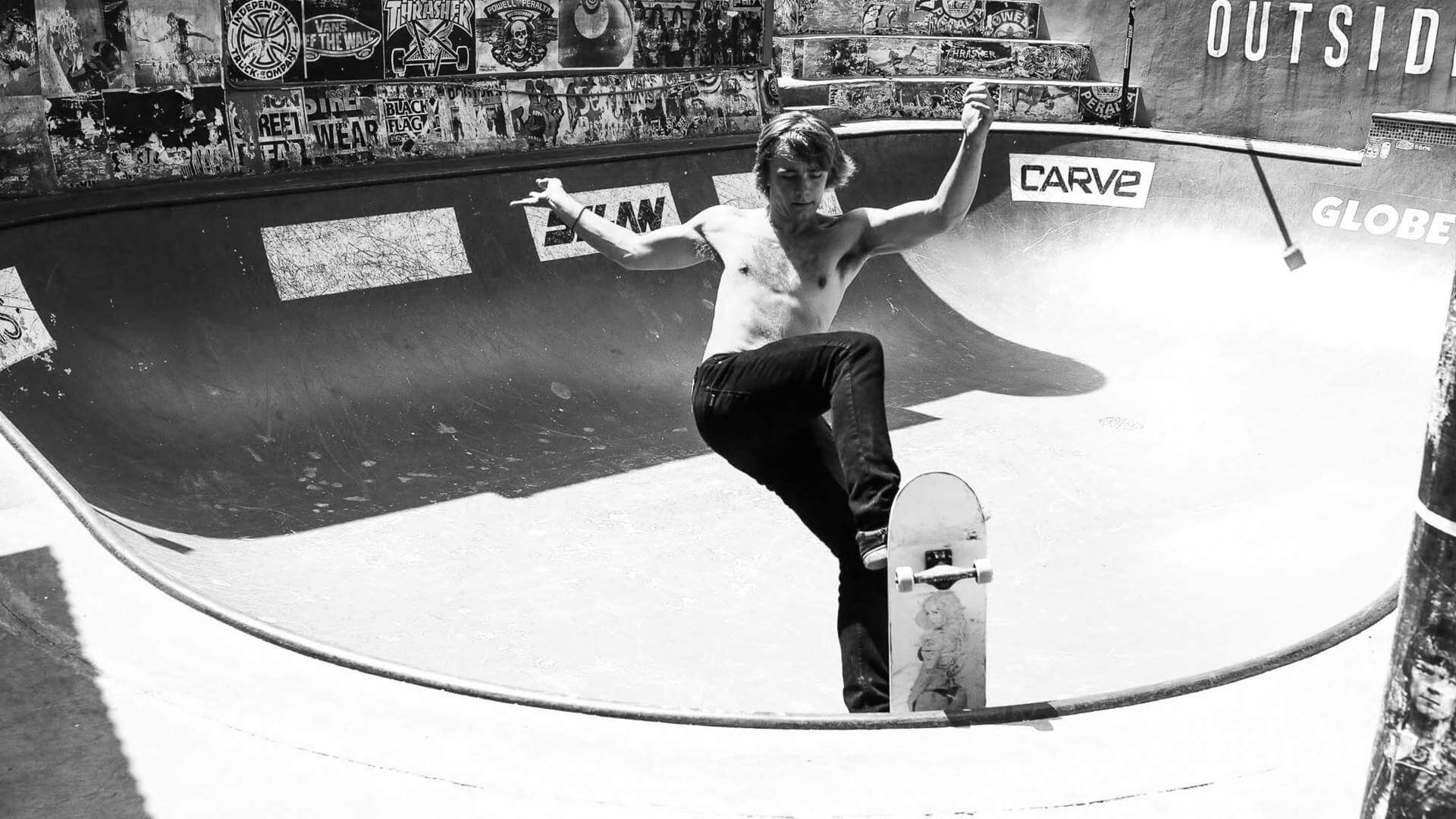 Black and white photo of a guy skating without a shirt in Uluwatu.