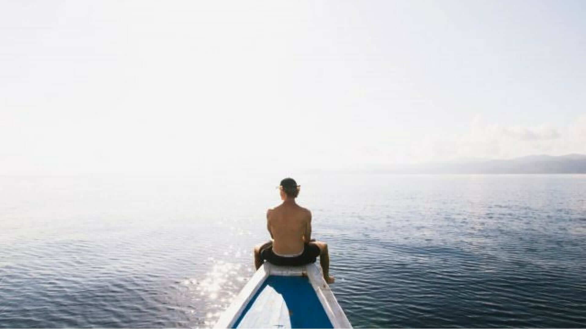 A man sitting at the end of a boat watching over the sea in Bali.
