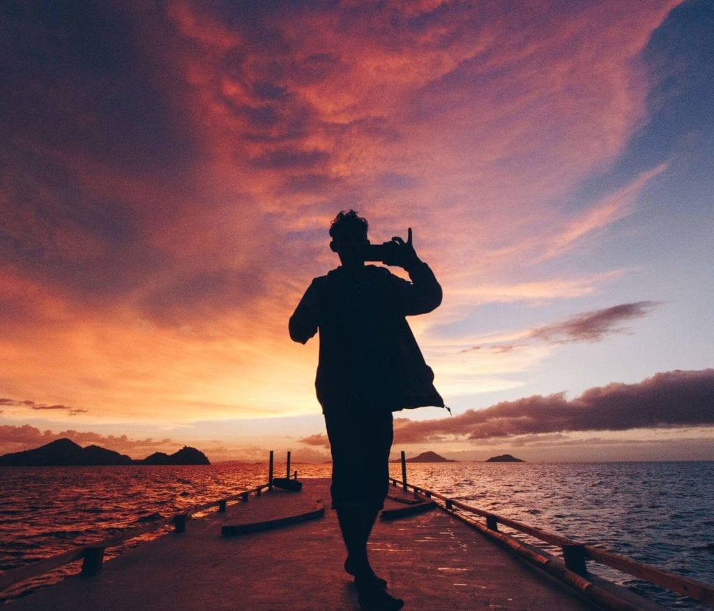 Man taking a picture of the sunset with a cloudy sky