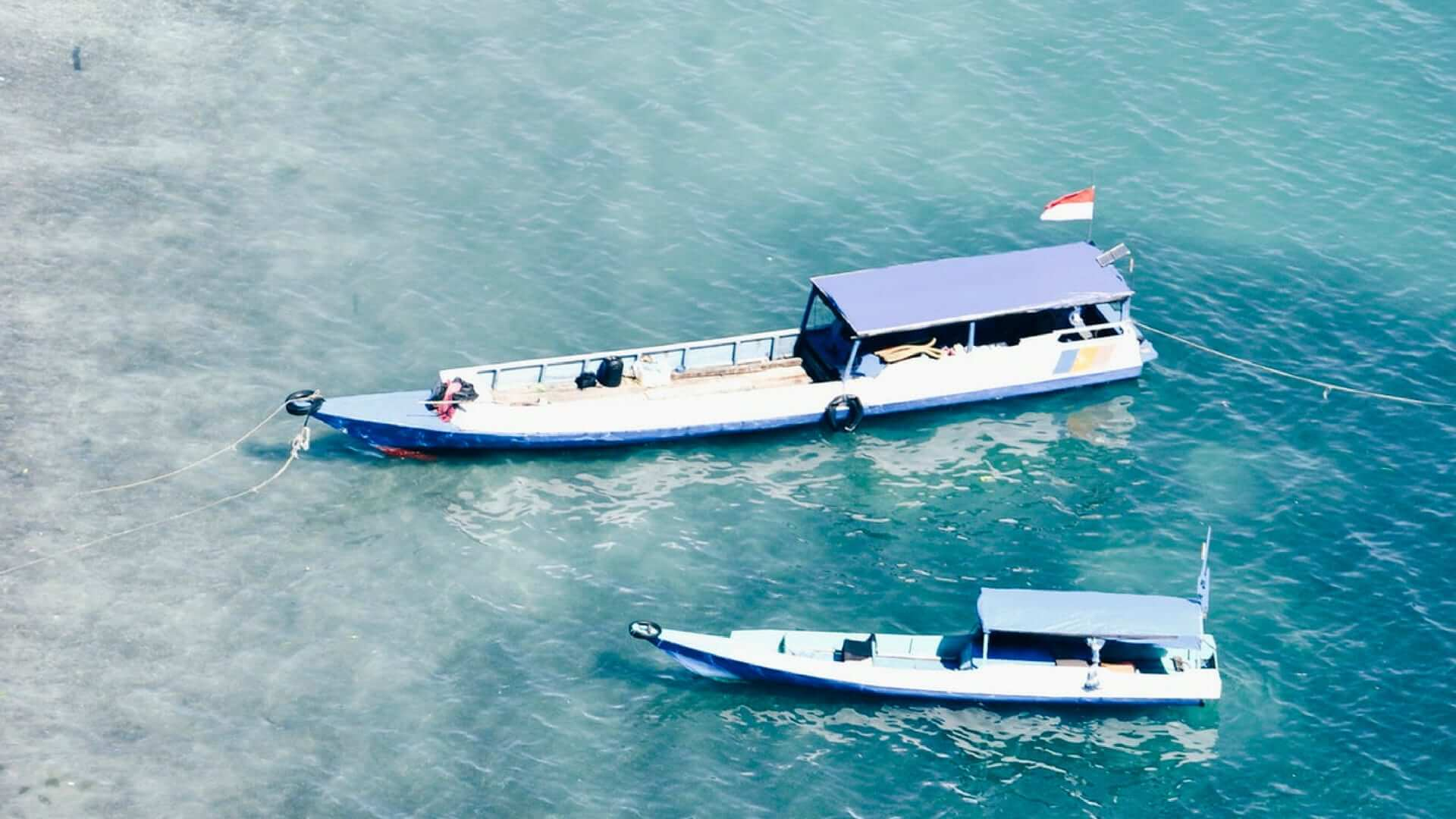 Two boats are laying in the water near Komodo Island.