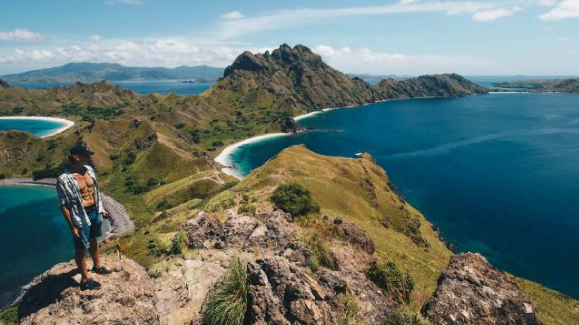 A student is standing in front of an overview of Padar Island.