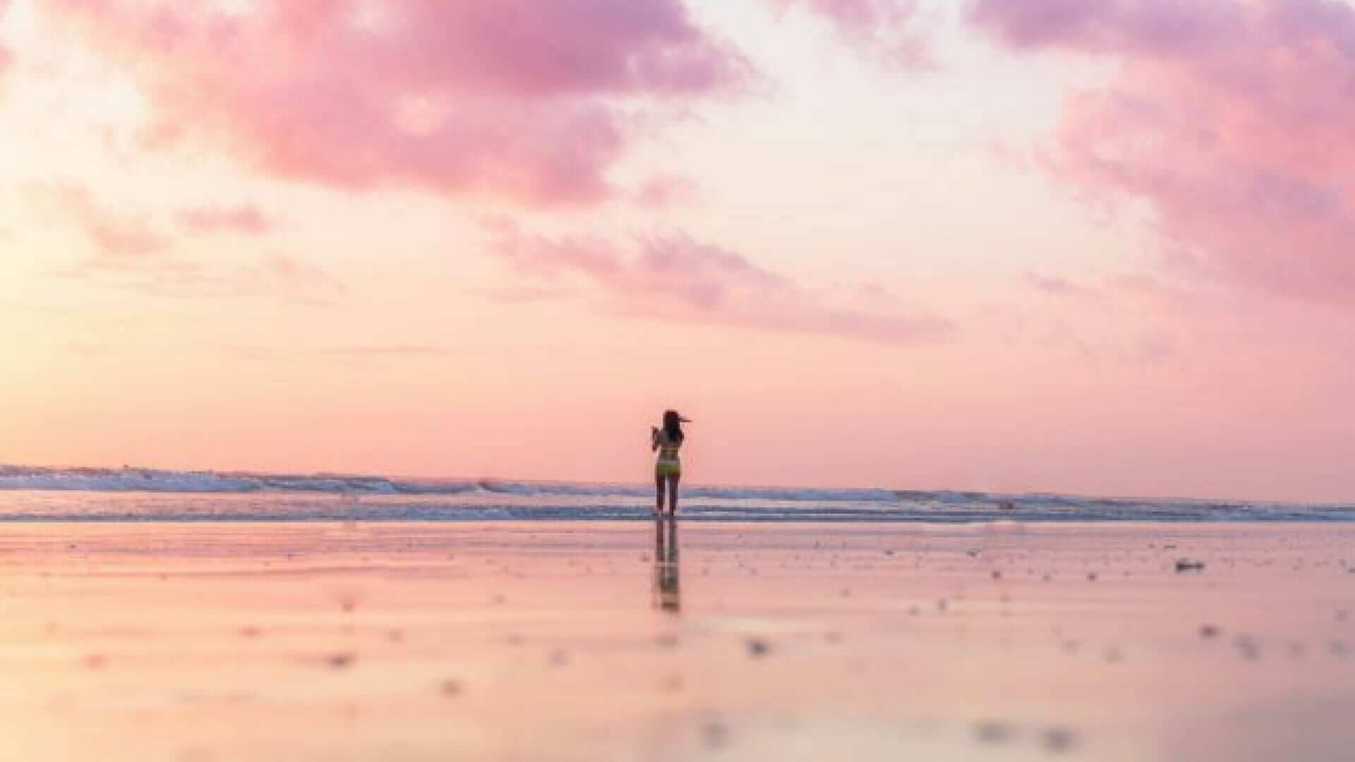 A girl is looking over the water while she is standing on a pink beach.