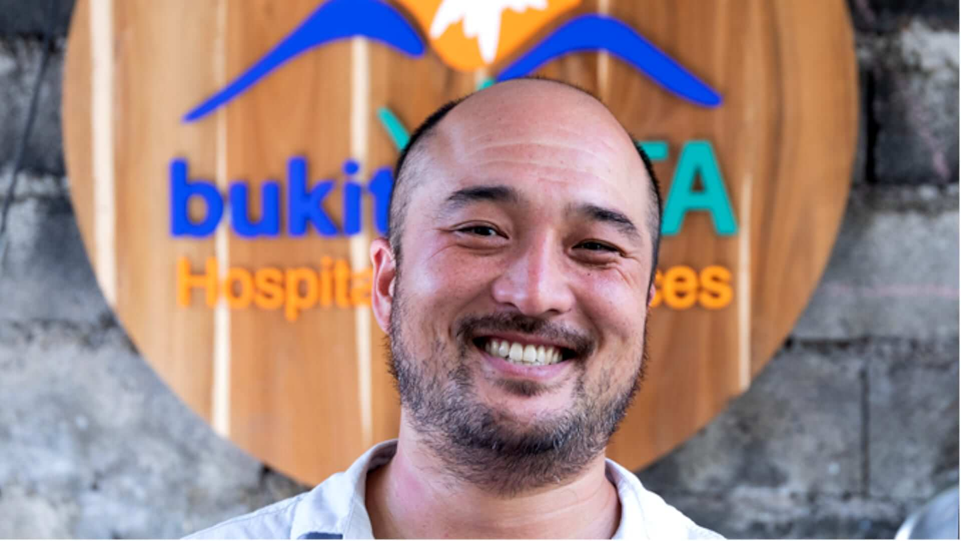 Owner of Bukit Vista company smiling in a picture with the company logo in the background.