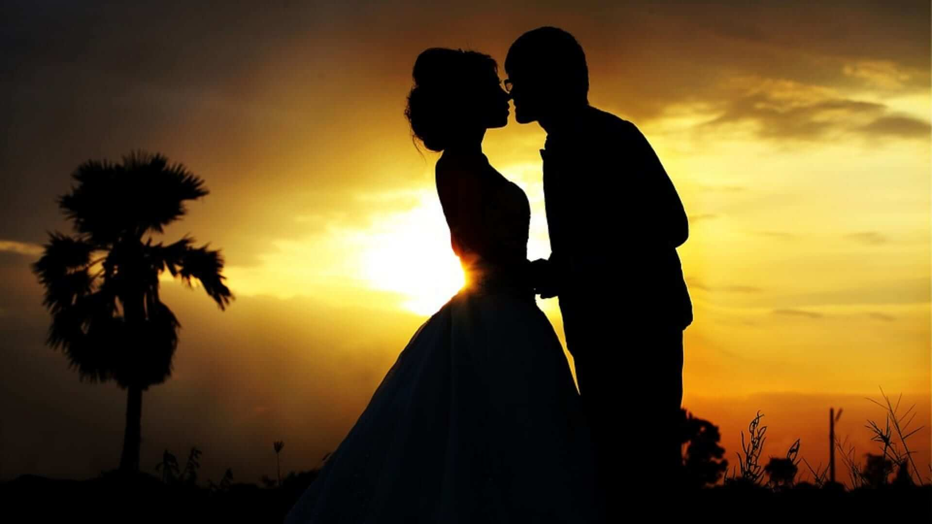 A silhoutte of two people kissing during sunset in Thailand.