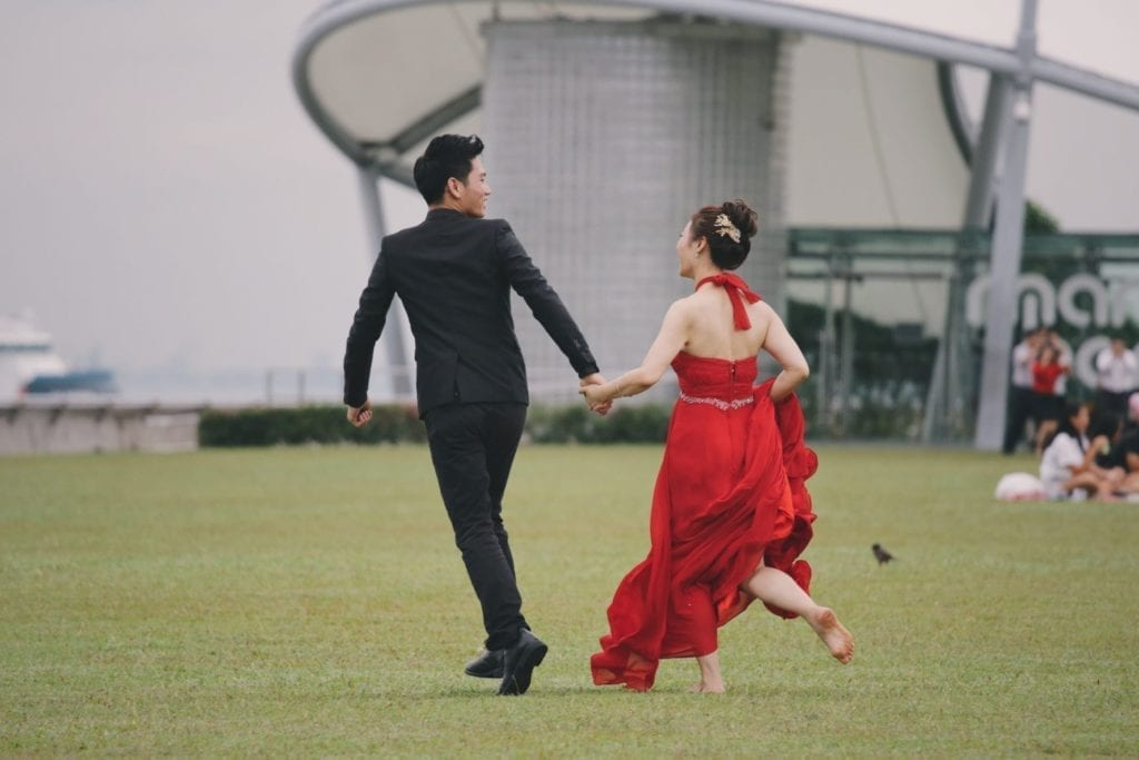 Guy dressed in black and girl dressed in red running on grass