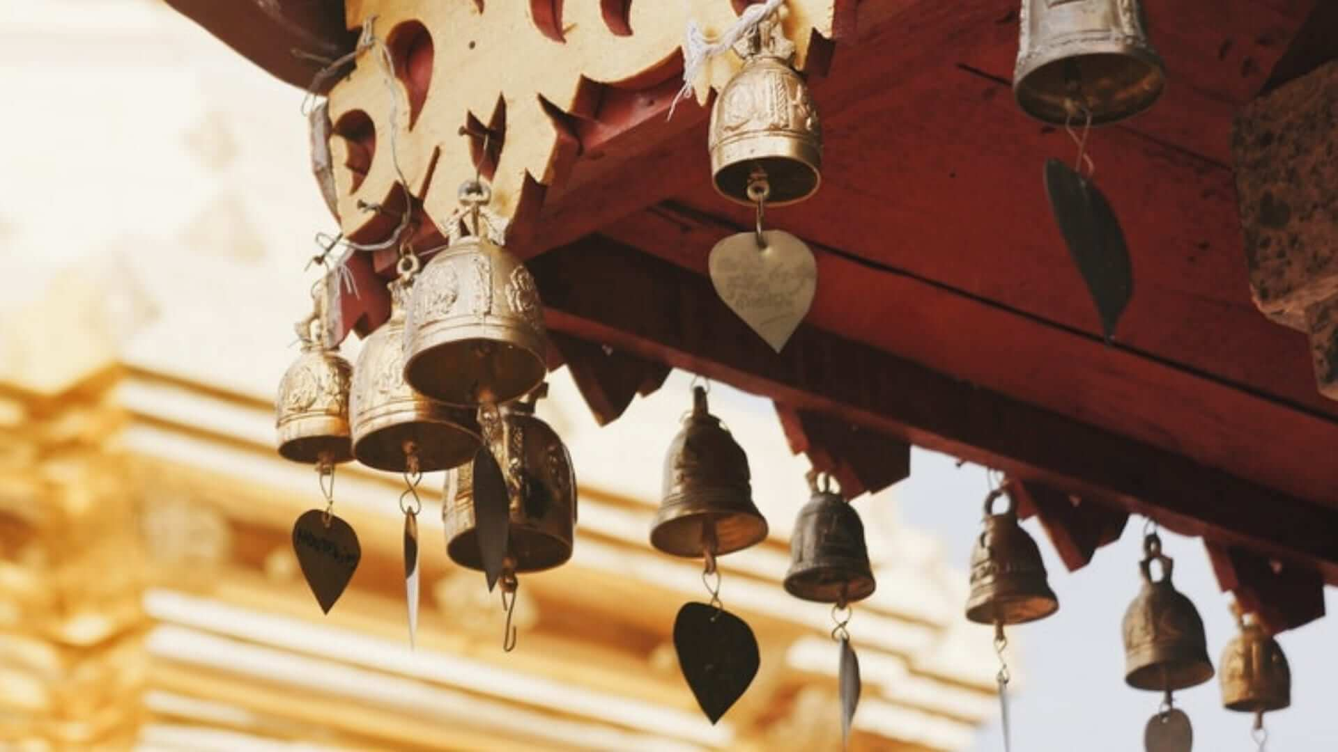 A close-up picture of bells and hearts hanging under a roof as decoration in Thailand.